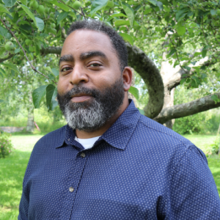Dr. Steven Oliver stands in front of a green apple tree in summertime