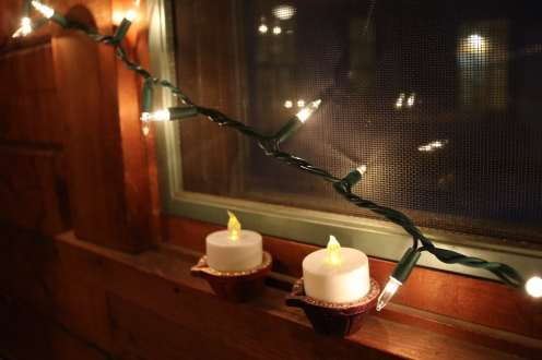 Two candles in the window with twinkle lights hanging on top of them for the celebration of Diwali.