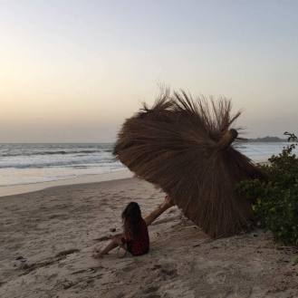 Photo of student Anushka sitting under a thatched roof on the beach in Senegal at sunset. The waves are crashing.