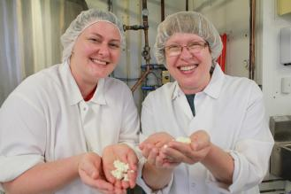 two women with hairnets and white coats holding cheese curds in a cheese facility