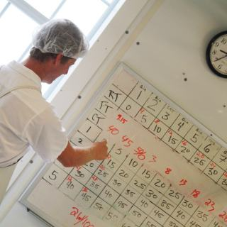 a man in cheesemaking coat and net hat updating records on a whiteboard