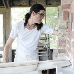 Richard Miscovich, baker and author, a man wearing a white shirt with glasses and a ponytail with one arm in a wood-fired oven