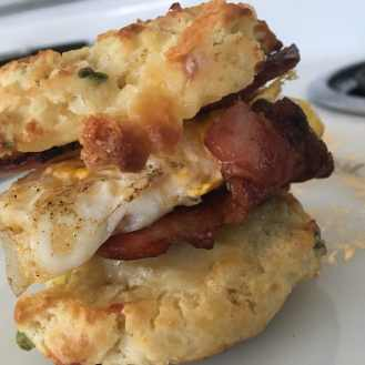 picture of a fluffy, cheesy, perfectly golden Spring Onion Biscuits sandwich, with egg , bacon, and more cheese