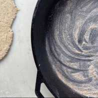 a photo of the cast iron skillet used to bake sourdough discard crackers. The skillet is greased and line with a think layer of cornmeal.