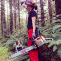 Woman wearing orange chaps and helmet holding a chainsaw. Softwood forest and large green ferns in background.