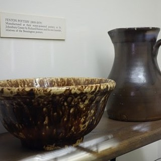 2 pieces of pottery on a display shelf. Brown and white mottled bowl and matte brown vase. Small placard in background.
