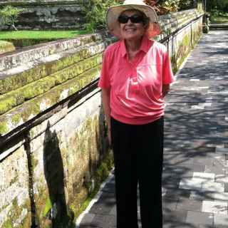 Joan is wearing a pink polo and black pants, sunglasses, and a brimmed hat