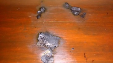 Scorch marks on the fireplace. The melted wax was dripping through these holes this morning