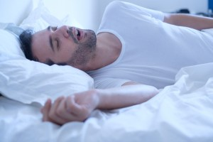 man sleeping and snoring in bed with white sheets
