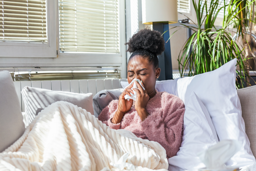sick woman experiencing sinus issues blowing her nose