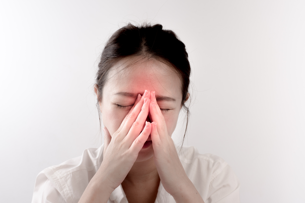 woman holding nose due to sinus pain