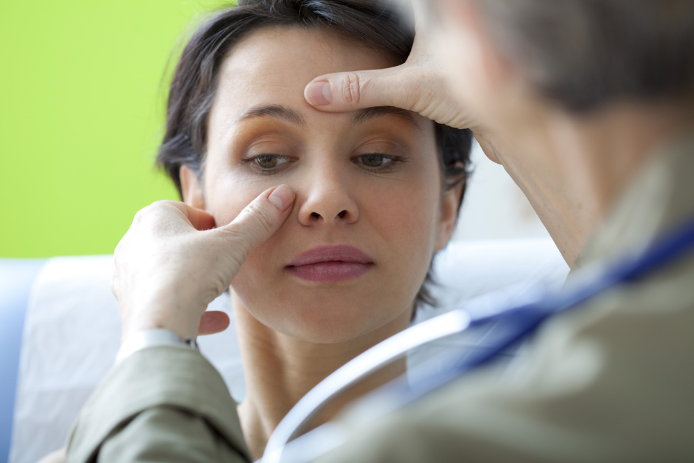 Doctor checking women's nose and sinus with fingers