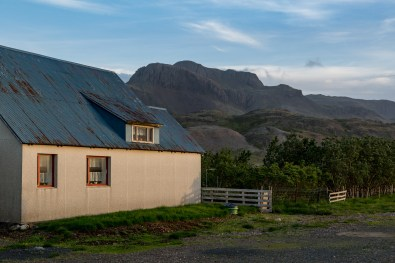 The house, nestled against the mountains in Þvottá