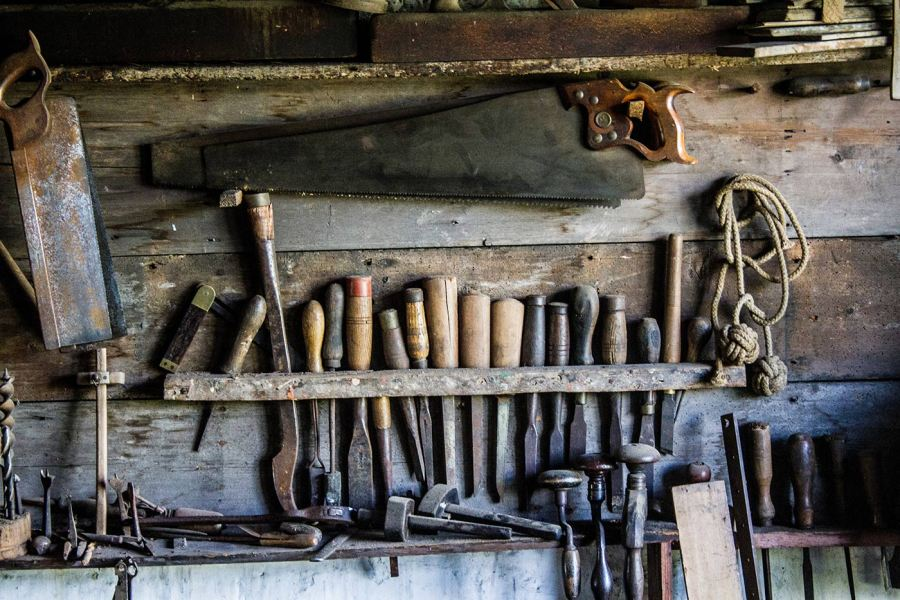 Various woodworking tools hung on a woodshop wall
