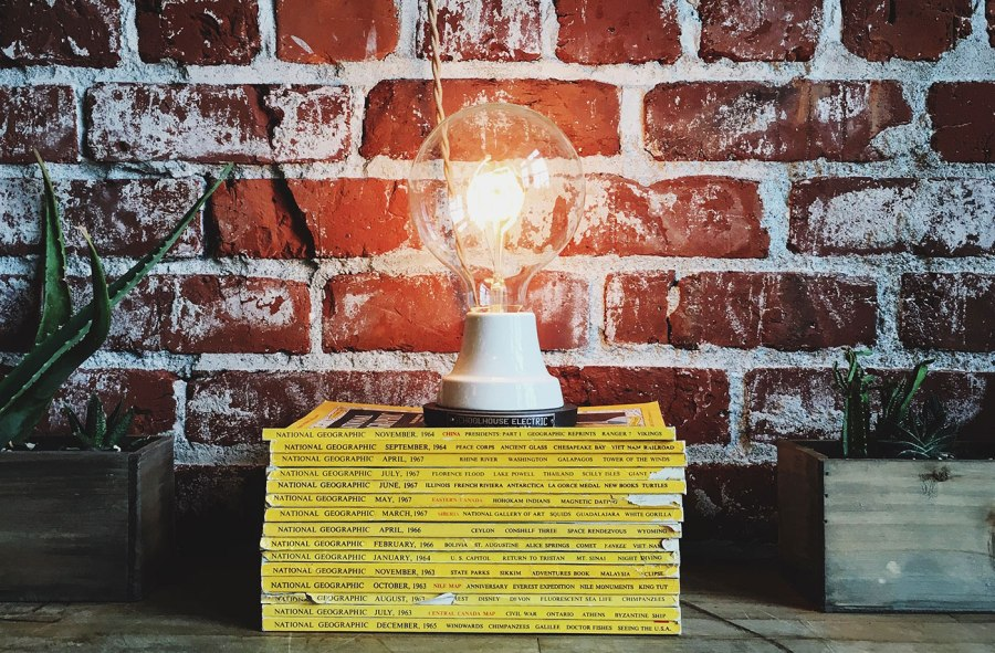 An exposed lightbulb sitting atop a pile of books