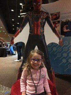 My daughter standing in front of a Spider-man cardboard cut-out at a sponsor booth