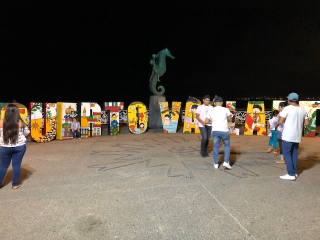 The Puerta Vallarta sign at the Malecon, with the dolphin sculpture in the middle