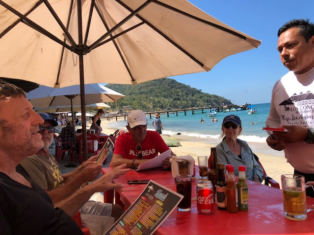 Everyone pictured except Richard, the waiter is taking orders. You can see the water and pier in the background.