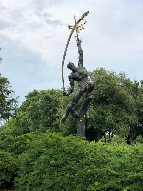 Beautiful and huge statue in the park, of a man hurling a rocket