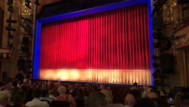The stage: red curtain with a cream colored band along the bottom, maybe 3 feet high. Stage framed in blue light.