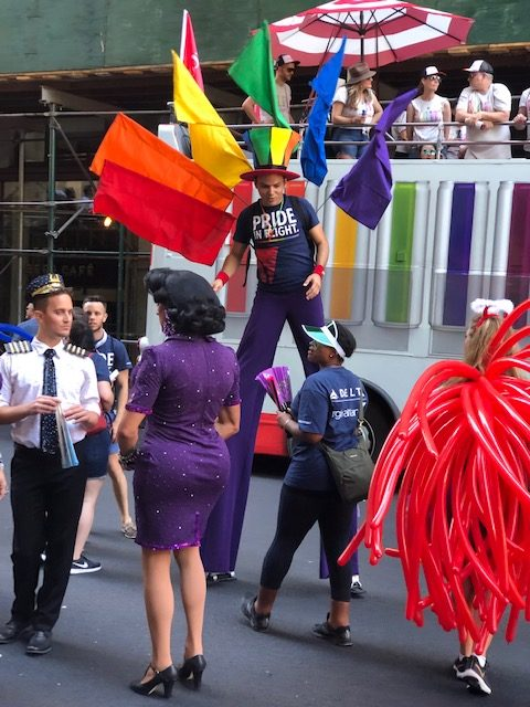a guy on stilts with 6 flags sticking out of his bag in a peacock array, one for each of the rainbow colors