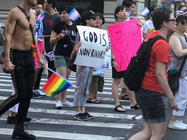 """Chinese woman carrying a sign that says """"God is non binary"""""""