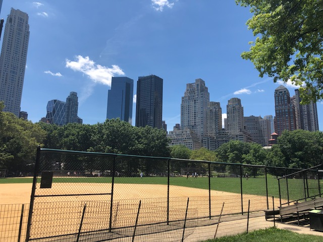 A baseball diamond with skyscrapers beind it