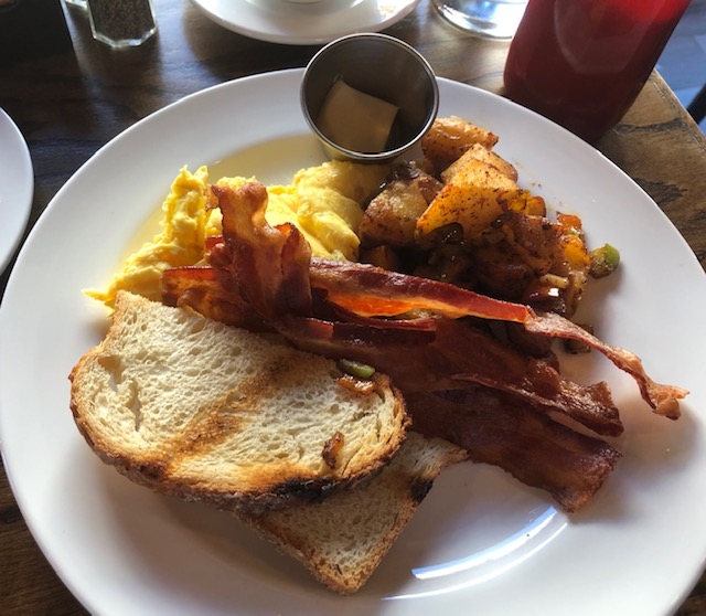 Breafkast: scrambled eggs, bacon, potatoes, sourdough toast