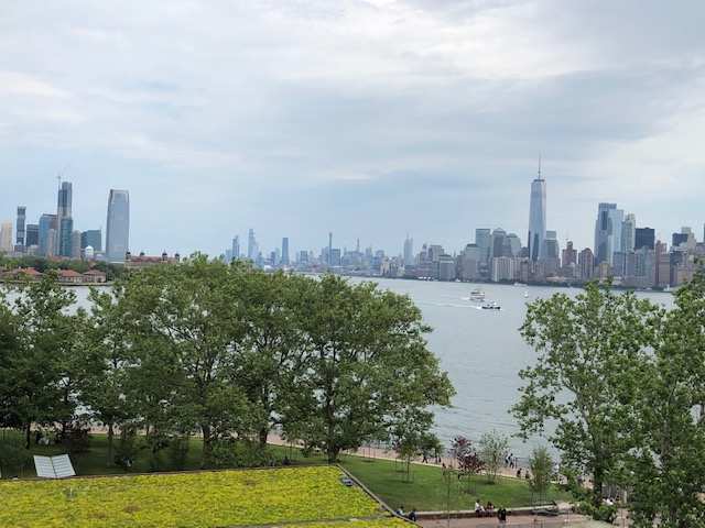 Jersey City and NYC in the background, trees and grass in the foreground from the park