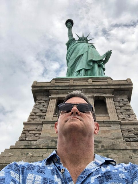 Selfie standing close to the pedestal looking forward, the statue looming over my head behind me