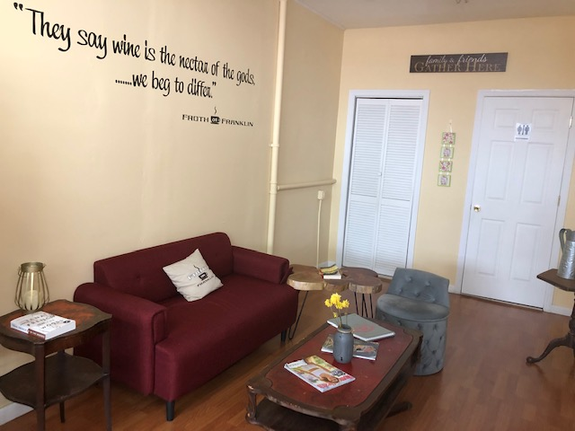 A maroon couch against the wall, coffee table in front of it, small chair to the left side of the table; door to restroom in the far right corner