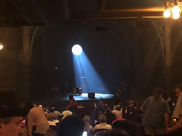 A beam of light form a perfect circle in the back wall streaming down onto the stage