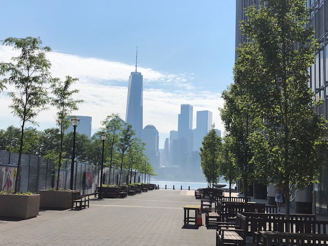 World Trade Center from Jersey City, framed by a tree lined walkway, and a tall buildin on the right