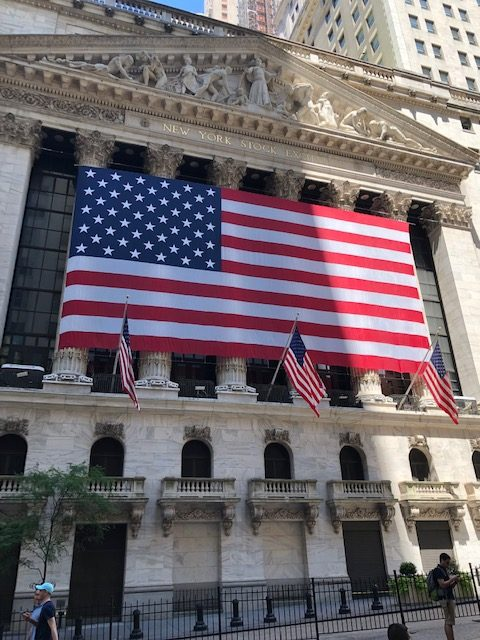 The New York Stock Exchange building, much of it covered in a huge USA flag