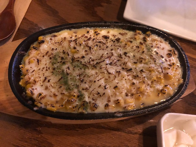 A small skillet with a dish called sizzling cheese corn; you can see yellow corn in sauce, white cheese, slightly burnt on top
