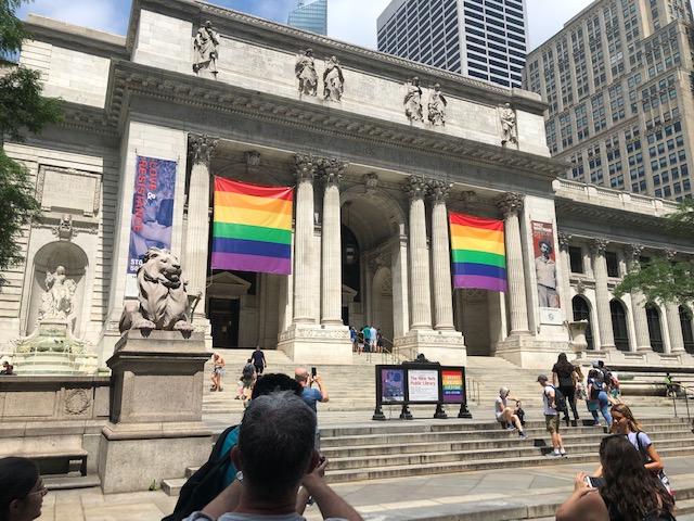 The New York Public Libray, with 2 large rainblow flags hanging between the front columns
