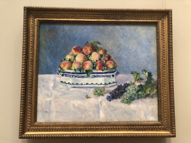 peaches in a white bowl with decorative blue trim, purple and green grapes lieing being is on a white tablecloth