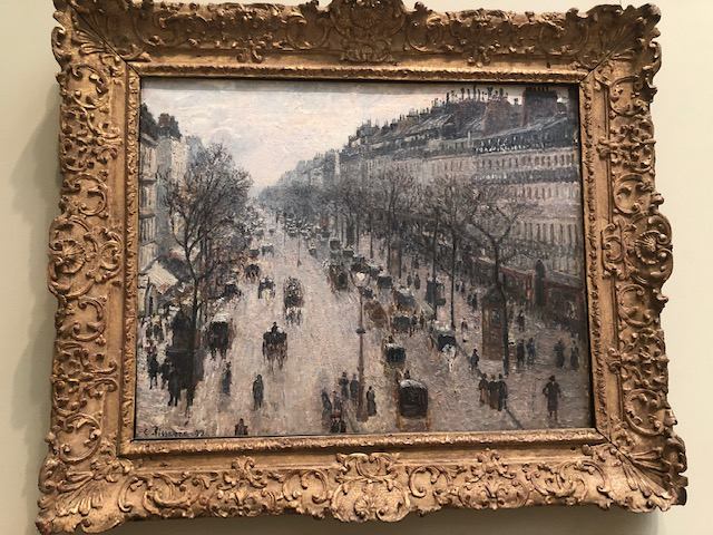horse and buggies moving up and down a Paris street in winger; mostly shades of gray