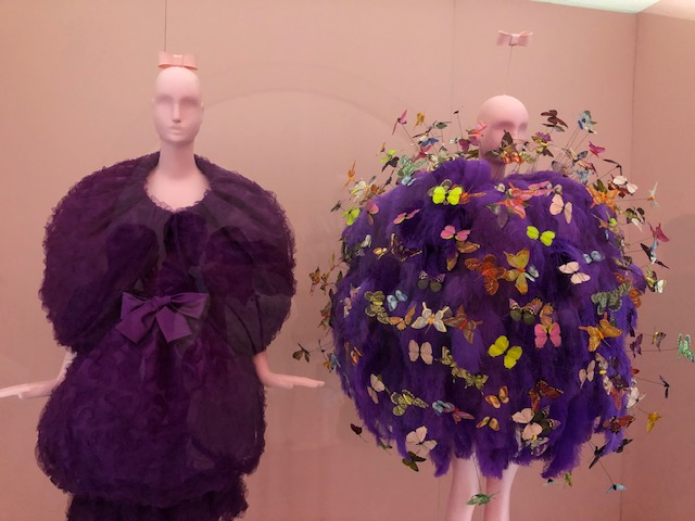 2 mannequins dressed in purple, the first in a formal 60's chic style, puffy lace with a big bow in the middle; the 2nd a big puff ball of boas maybe with butterflies on sitcks sticking out all over