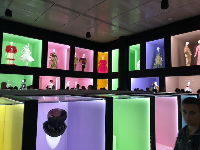 A large room with 2 levels of square windows, like department store sidewalk windows. Walls are black and room is unlit except for the light coming from the windows. 1-3 Mannequins in each window dressed in wide array of camp