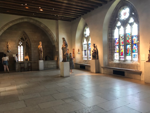 Room with stained glass windows and many sculptures