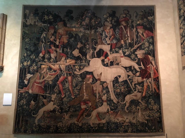 Tapesty of a unicorn fighting dogs, and men with weapons