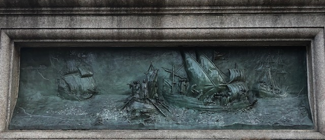 Closeup of a bronze relief done of ships from 1492, on the pedestal