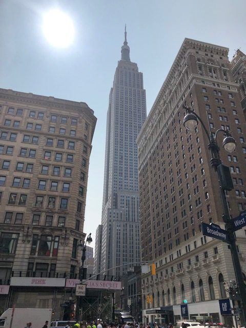 The Empire State Building in the background between two other buildings on either side in the foreground; sun shining brightly top left