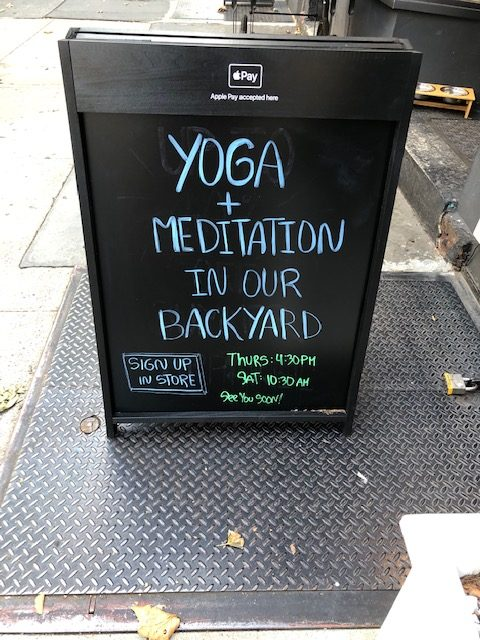 """Sandwich board on the sidewalk that says """"yoga and meditation in our backyard"""" with a schedule."""