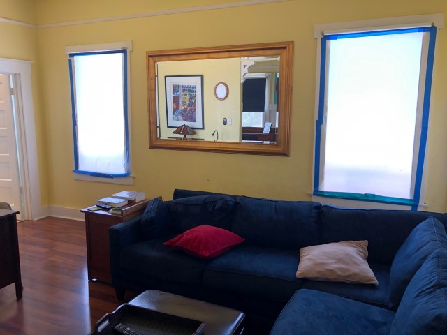 living room showing south windows covered with white paper, framed by blue masking tape - no windows