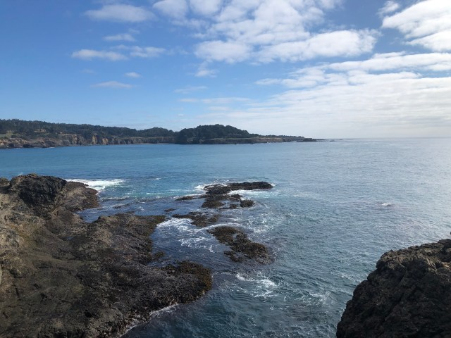 cliffs in the foreground, rocks in the middle, land in the background, ocean in the middle