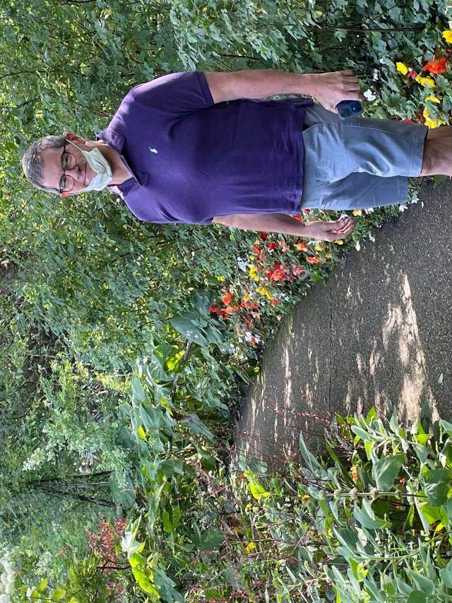 Me wearing a purple polo, gray shorts, and a big smile, walking along one of the paths with flowers on either side.