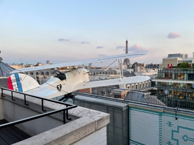 A bi plane propped on the roof of the building with the Eiffel tower in the background.