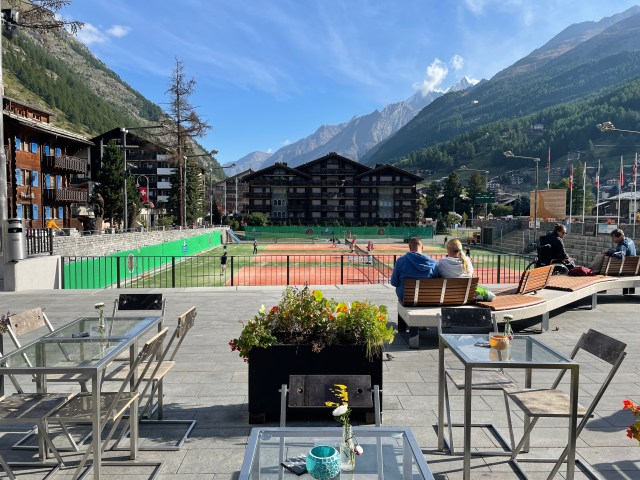 tables and chairs on a wide sidewalk, tennis courts behind that, hotels and mountains behind that
